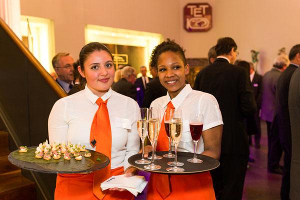 Kellnerinnen bringen Fingerfood und Sekt