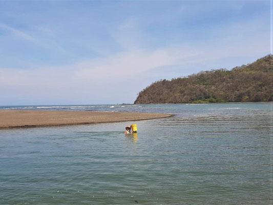 Auf dem Rückweg ist das kleine Gewässer zu einer grossen Flüssmündung angewachsen - Röbä bringt unsere Sachen in einem Eimer ans andere Ufer