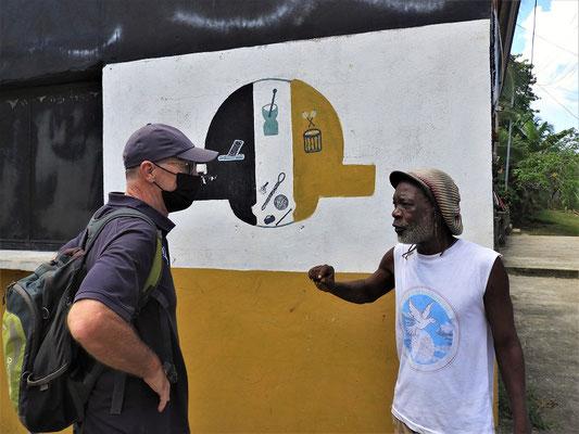 Philip - ein Garifuna - führt uns durch seinen Stadtteil und erklärt uns hier das Wappen der Garifuna