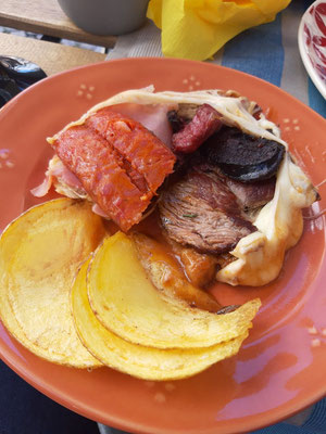 Zwei Scheiben Toast, Schinken - hier Steak und Würste - mit viel Käse überbacken, in einer Sauce aus Tomaten, Bier und Senf