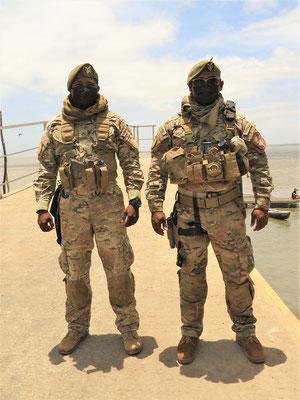 Diese zwei bewaffneten Militär bewachen den kleinen Hafen