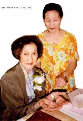 平成5年に発見された一羽の小さな折鶴を両手のひらに乗せる岡本三典氏。そのすぐ傍らの女性。折鶴を発見し、岡本氏の元に届けた。書籍『死んでも生きているいのちの証し』『神秘の大樹』の著者夫人である。いずれの著書からも読み取れる夫人の言動はまさに誠一筋。出典は『神秘の大樹 第二巻 ヒロシマとつる姫』