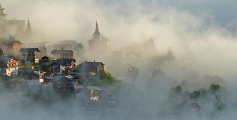 Morgennebel nach einer Gewitternacht umströmt das Dorfzentrum von Zeneggen