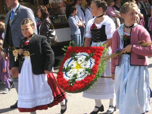 Herbstfest Rosenheim: Erntedankfestumzug, Kinder tragen das blumenverzierte Stadtwappen