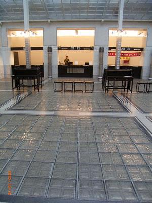 ホールのガラスブロックの床。柱被覆と暖房給気筒はアルミ板加工