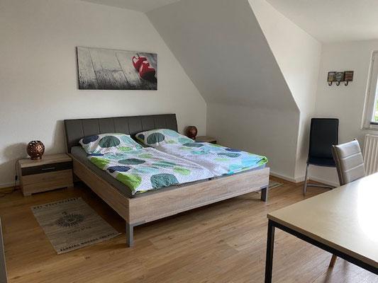 Blick in das Schlafzimmer mit großem Doppelbett
