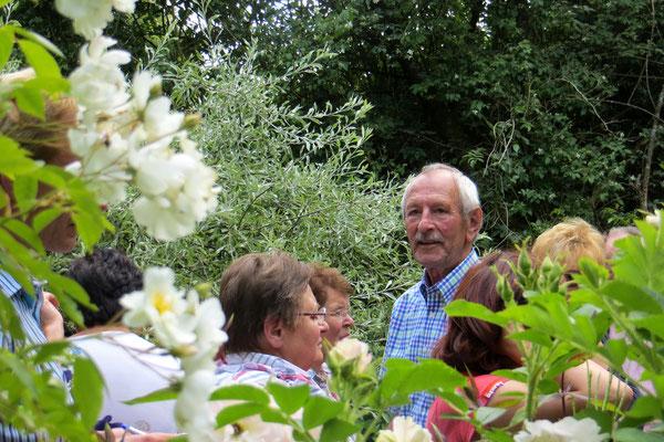 Unser Reiseleiter Manfred ragt zwischen Rosen und Rosenfreunden heraus