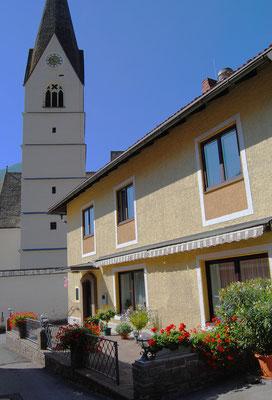 Pension Kirchenwirt Außenansicht mit Pfarrkirche Obervellach