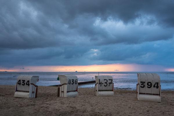 Dramatische Regenwolken, Strandkörbe und Sonnenuntergang am Strand Hooksiel