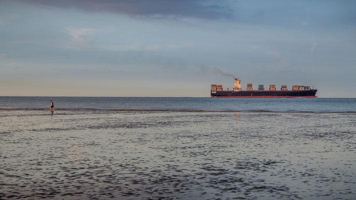 Containerschiff fährt zum Jade-Weser-Port am Strand von Hooksiel