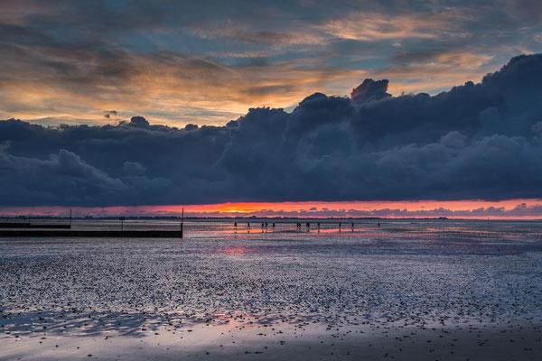 Wattwanderung bei Sonnenuntergang am Strand von Hooksiel