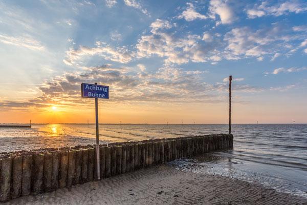Sonnenuntergang an der Buhne am Strand Hooksiel