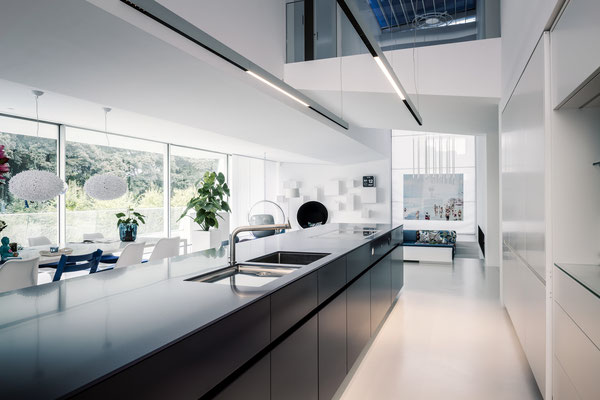 Die stahlblaue Küche als Blockkörper, die Nebenfunktionen der Küche dahinter, Foto: Daniel Hartz