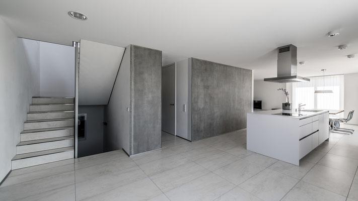 Die geschliffene Betonwand mit Garderobe, Gäste-WC und dem offenen Treppenhaus, Foto: Aryan Mirfendereski