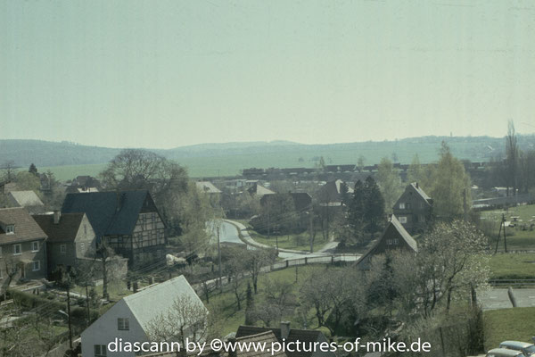 Blick aus dem elterlichen Küchenfenster in Lohmen Richtung Bahndamm. Eine V100 und eine V60 ziehen einen Güterzug in Richtung Dürrröhrsdorf / Neustadt. Aufnahme Mai 1987