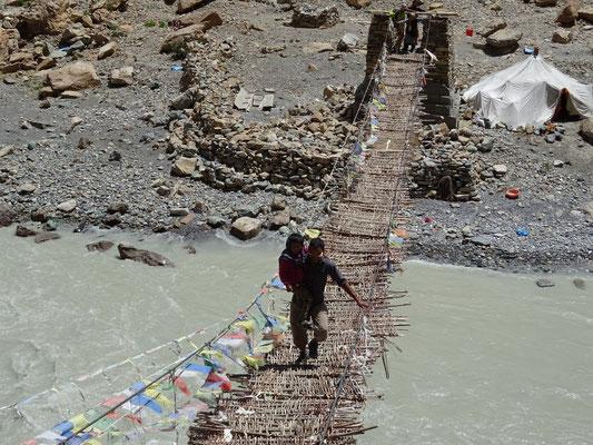 Dordjé prend soin de la petite fille pour traverser ce pont suspendu