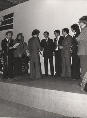 J.BOLLE: Remise des prix Challenge Honda France 125 1976 - de G à D: Speaker, D.BLANC, J.P.BRUNIER (organisateur Challenge), J.BOLLE (de dos), Responsable Honda, X, F.BELLIN (Dunlop), M.SEGURA (Cuir), PRIOUX (Total)