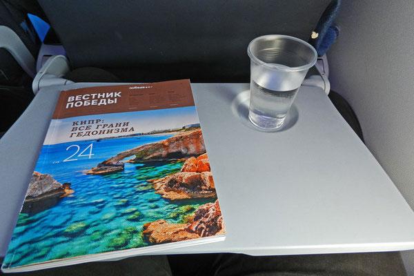 Der bescheidene Bordservice: Ein Glas stilles Wasser und ein Blick in die Bord-Zeitschrift