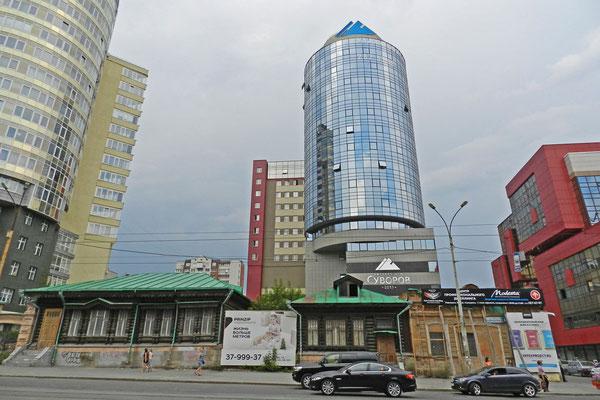 Holzhäuser vor neuen Hochhäusern in Jekaterinburg