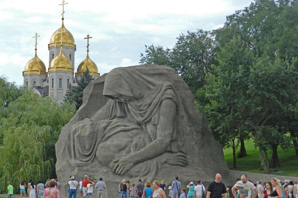 Das Denkmal der trauernden Mutter mit der neuen orthodoxen Kirche