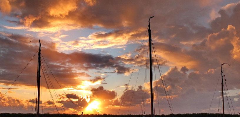 Mooie luchten achter de masten van de schepen in de haven van bij Noordpolderzijl.