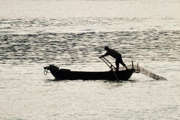 Een visser zet zijn netten uit.