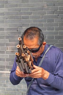 Straatmuzikant met een mondorgel