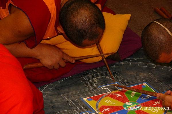Met uiterste precisie brengen de monniken een stroom gekleurde zandkorreltjes via een metalen buisje op de juiste plaats in de mandala. Mond- en neuskapjes moeten verhinderen dat het zand van zijn plaats wordt geblazen en het patroon van de mandala versto