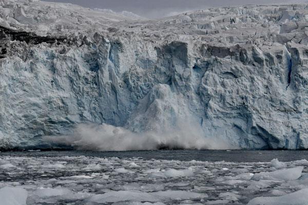 Een stuk van een gletsjer breekt af.