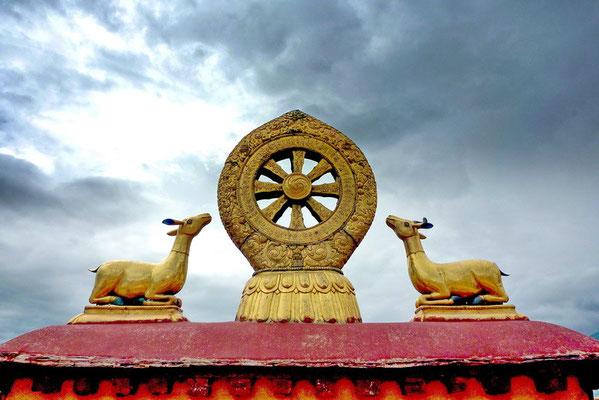 De kalachakra; het achtspakige wiel der wet met de herten die verwijzen naar Sarnath.