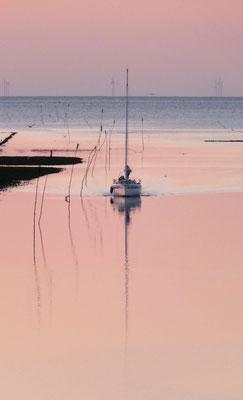 Een passant komt de haven in om de nacht door te brengen. Op de achtergrond de windturbines op de Noordzee.