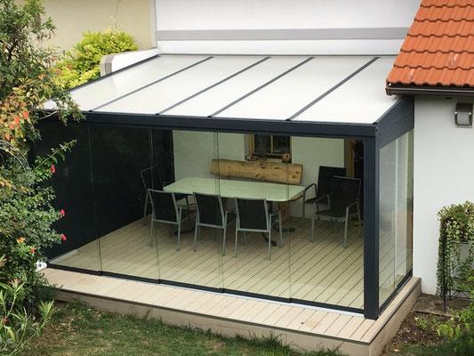 Sommergarten mit rahmenlosen Glasschiebewänden