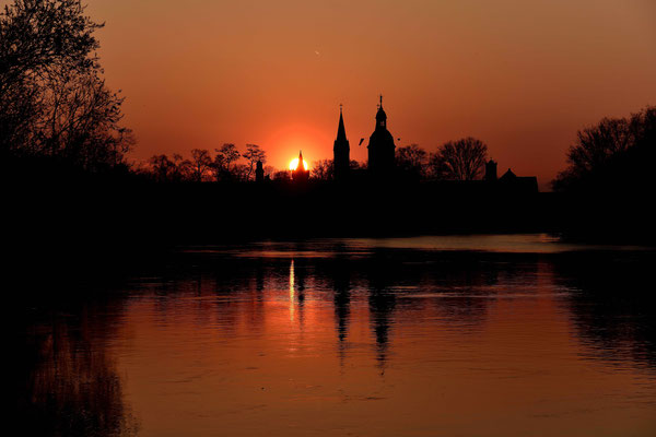"""Hinter der """" Basilika """" geht die Sonne unter, im Vordergrund ist der Main."""