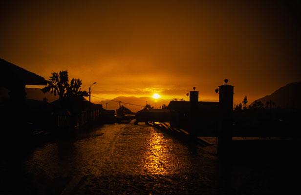 Nach einem Regenschauer kommt in Putre am Abend die Sonne noch heraus und taucht alles in ein orangenes Licht.