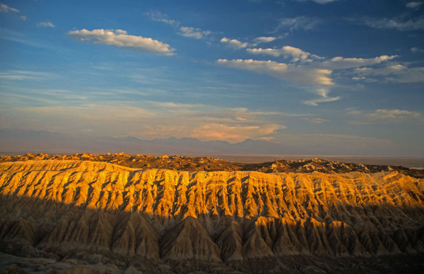Die Sand und Stein Landschaft wird von den Farben der untergehenden Sonne angeleuchtet.