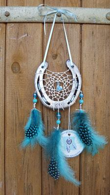 Glücksfänger Sun mit weißem Baumwollgarn, Glasperlen in verschiedenen Türkistönen und in der Mitte einer Fuchs-Keramikperle. Die Federanhänger sind mit Flausch- und Perlhuhnfedern gestaltet. Als Aufhängeband dient hier ein schmales Schleifenband.