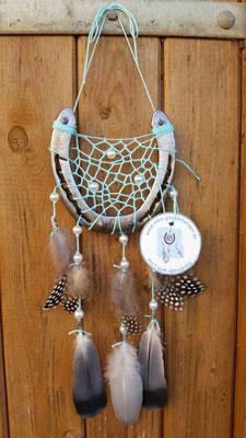 Glücksfänger Sun mit türkisenem Baumwollgarn, Holzperlen in Perlmuttweiß und Ornamentmetallperlen. Die Federanhänger sind mit Perlhuhn- und Taubenfedern gestaltet. Der Anhänger weist ihn als Original-Glücksfänger aus.