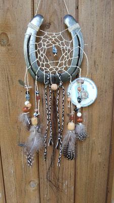 Glücksfänger Sun mit beigem Baumwollgarn, Holzperlen in Naturtönen melierten Kunststoffperlen. Die Federanhänger sind mit Perlhuhnfedern, Hufnägeln und Münzen gestaltet. Geflochtene Bänder ergänzen die Anhänger Der besondere Clou ist die Pferdehaarsträhne