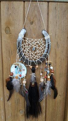 Glücksfänger Sun mit beigem Baumwollgarn, Holzperlen in Naturtönen melierten Kunststoffperlen. Die Federanhänger sind mit Perlhuhn- Fasanen- und Hahnenfedern, Hufnägeln und Münzen gestaltet. Der besondere Clou ist die Schweifhaarsträhne.