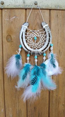 Glücksfänger Sun mit weißem Baumwollgarn, weißen Perluttperlen, türkisen Keramikperlen sowie Ornamentmetallperlen. Die Federanhänger sind mit weißen Flauschfedern und türkisen Perlhuhnfedern gestaltet. Ein Original-Glücksfänger mit Anhänger.