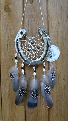Glücksfänger Sun mit weißem Baumwollgarn, weißen, schwarzen und beigen Holzperlen sowie Ornamentmetallperlen. Die Federanhänger sind mit Tauben und Perlhuhnfedern gestaltet. Der Anhänger weist ihn als Original-Glücksfänger aus.