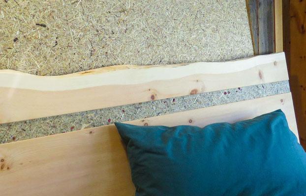 Zirben-Kopfteil mit Streifen aus echten Almheu vor einer Wandverkleidung mit Heu-Oberfläche