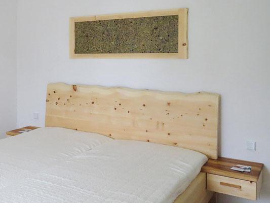 Almkräuter-Paneel als Bild im Zirbenholzrahmen, darunter ein Zirbenbett mit Naturkante