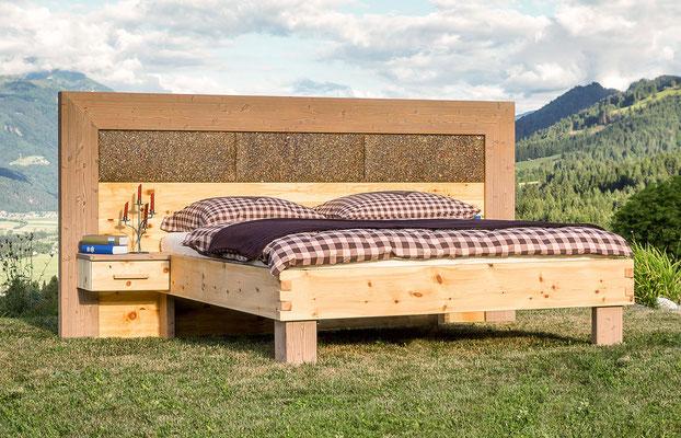 Zirbenbett mit Kräuter-Kopfteil in einer Alpen-Landschaft