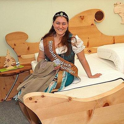 """Altmühlfränkische Bierkönigin Sarah auf dem Zirbenbett Bett """"Waldfee"""" am Stand von Möbel Meßmer auf der Messe"""