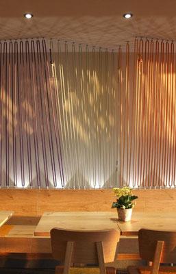 Dekorative Lichtwand mit bunten, gespannten Seilen im Restaurant
