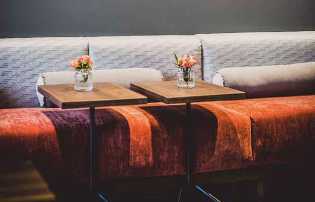 Sitzmöbel mit kleinen Beistelltischen aus dunklem Holz