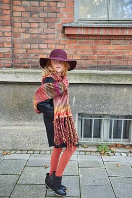 Mädchen in großem Schal und mit Hut