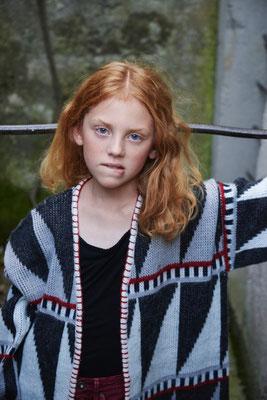 Mädchen mit roten Haaren in einer Strickjacke schaut frech in die Kamera