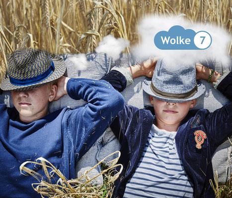 zwei Jungen liegen im hohen Gras im Sommer mit Hüten im Gesicht